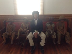 Jordan Bennett at Whitney Plantation with statues of slave children